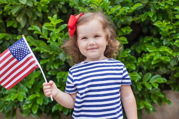 Adorable little girl holding american flag outdoors on beautiful summer day.