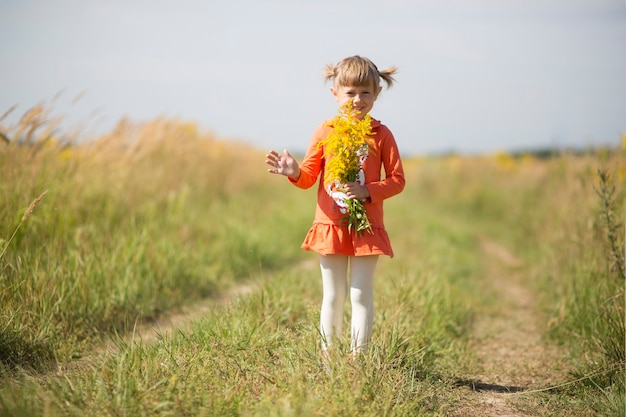 Adorable little girl holding a bouquet of yellow wildflowers in autumn field.