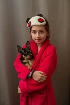 Прелестная маленькая девочка держа щенка чихуахуа стоя и смотря вверх. девочка держит собак чихуахуа на руках. девочка 9 лет с домашним животным дома на руках. понятие о любви к животным. дом