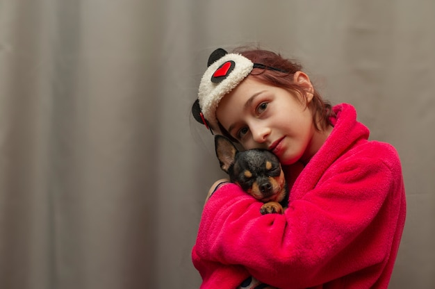 立って見上げるチワワの子犬を保持している愛らしい少女。彼女の腕にチワワ犬を保持している女の子。自宅でペットを腕に抱えた9歳の少女。動物への愛の概念。ホーム