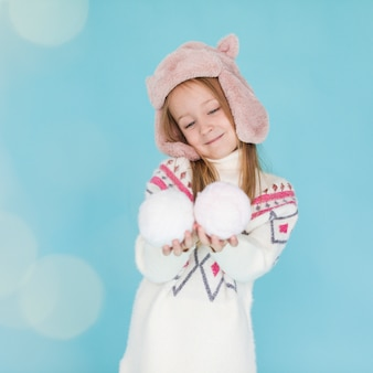 Adorable little girl holding snowballs