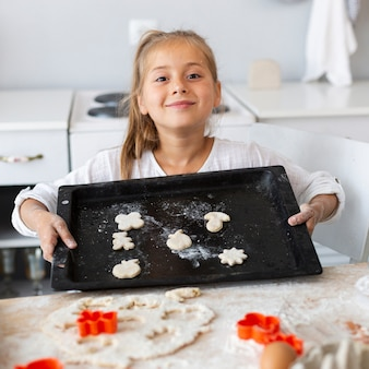 Adorable little girl holding tray with dough
