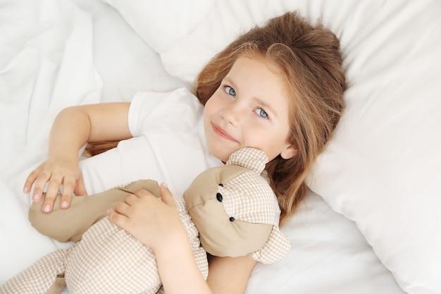 Очаровательная маленькая девочка обнимает плюшевого мишку в постели