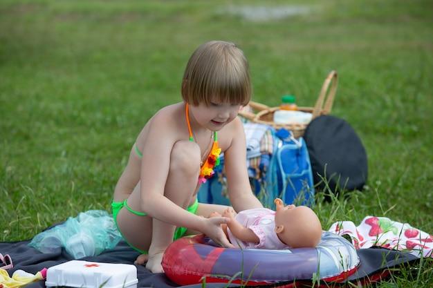 明るい水着姿の愛らしい少女が公園でのピクニック中にお気に入りの人形と遊ぶ