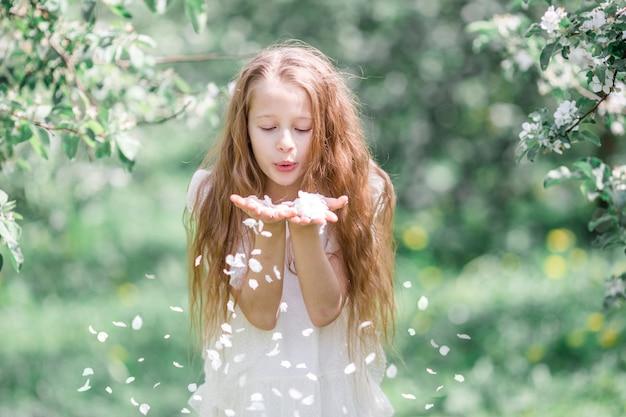 Очаровательная маленькая девочка в цветущем яблоневом саду в прекрасный весенний день