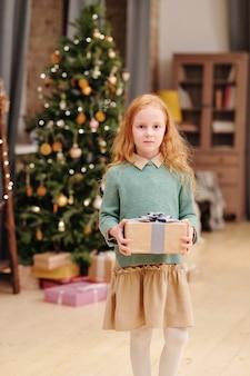 装飾されたファーツリーに立っている間、彼女の母親またはサンタからのクリスマスプレゼントとギフトボックスを保持しているカジュアルウェアの愛らしい少女
