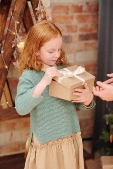 家庭環境でレンガの壁のそばに立っている間、彼女の母親からのクリスマスプレゼントでギフトボックスを開くカジュアルウェアの愛らしい少女