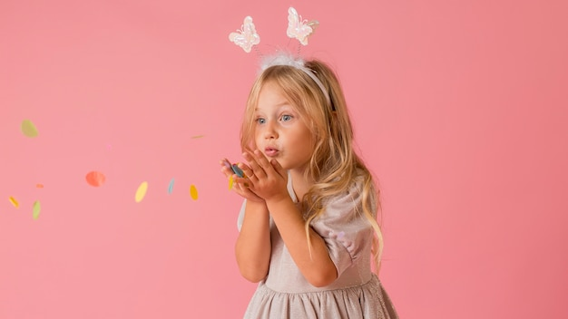 Очаровательная маленькая девочка в костюме дует конфетти