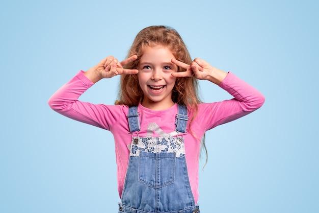 デニムの愛らしい少女が全体的に平和を楽しみながら2本の指でジェスチャーを踊る