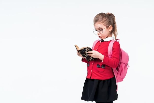 赤いスクールジャケット、黒のドレス、バックパック、ホワイトスペースでポーズをしながら本を感情的に見て丸みを帯びたメガネのかわいい女の子。隔離する