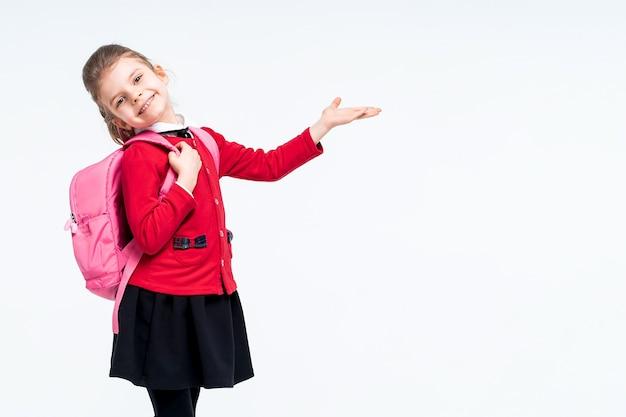 Очаровательная маленькая девочка в красной школьной куртке и черном платье-рюкзаке