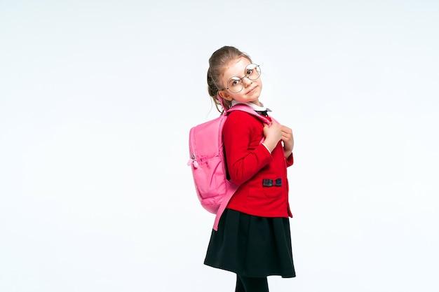 Очаровательная маленькая девочка в красной школьной куртке и черном платье с закругленными углами