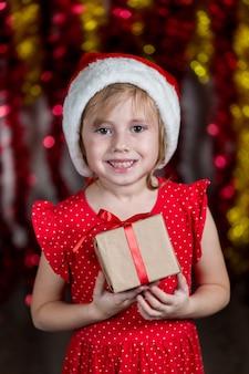 サンタハットの愛らしい少女は、夢のような顔をして新年のプレゼントを開催しています。