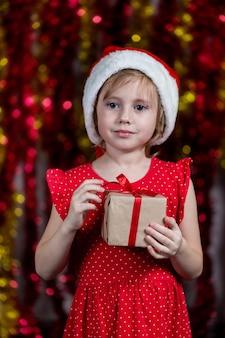Очаровательная маленькая девочка в шляпе санты держит новогодний подарок с мечтательным лицом.