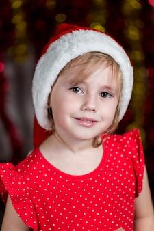 サンタ帽子の愛らしい少女が笑っています。