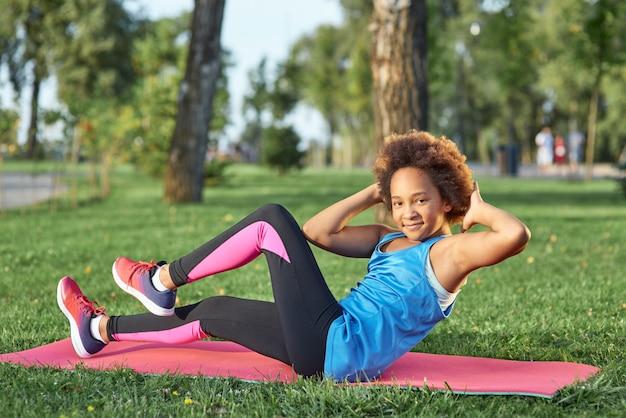 公園で運動をしているスポーツウェアの愛らしい少女