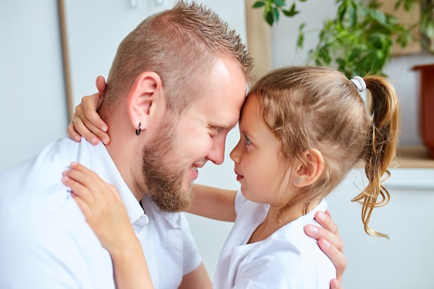 愛情と優しさで彼を見ている愛情のある父を抱き締める白いドレスの愛らしい少女