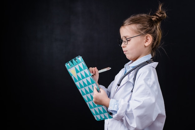 Очаровательная маленькая девочка в белом халате делает рецепты для своих пациентов в медицинском документе перед камерой