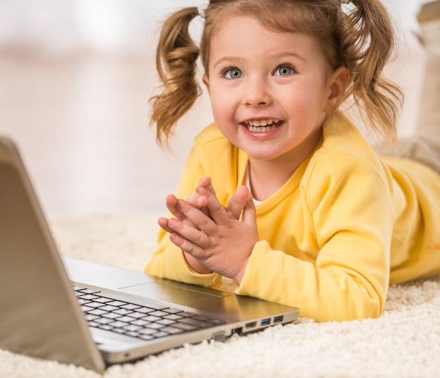 Adorable little girl is playing with laptop lying on floor.