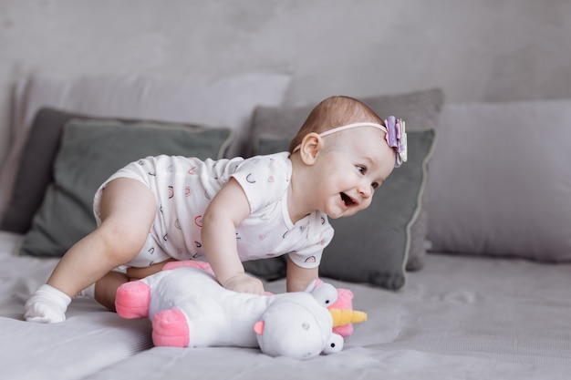 Adorable little girl is playing with toy unicorn on bed at home.