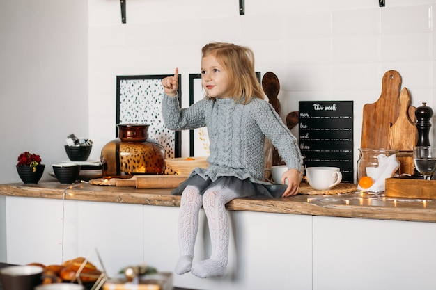 Adorable little girl is sitting on kitchen table. little girl in kitchen at home