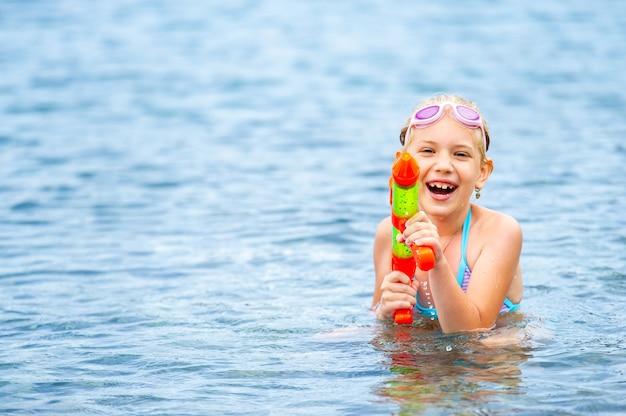 Очаровательная маленькая девочка плавает в море и играет с водяной пушкой. турция