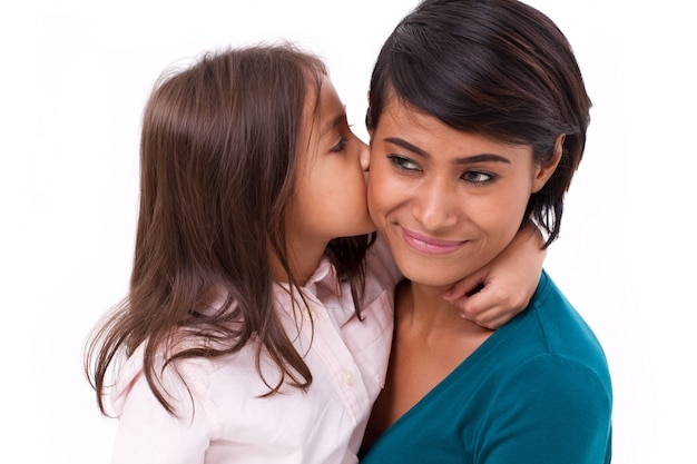 Adorable little girl kissing her mother's cheek