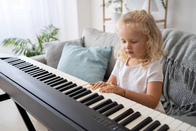 家でピアノを弾く方法を学ぶ愛らしい少女