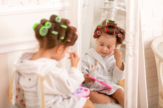 Adorable little girl learns to use baby cosmetics. beauty day.