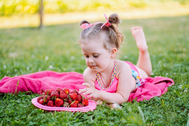 Adorable little girl lie on the grass with plate of fresh ripe strawberries and smile. childhood, immunity, happiness.