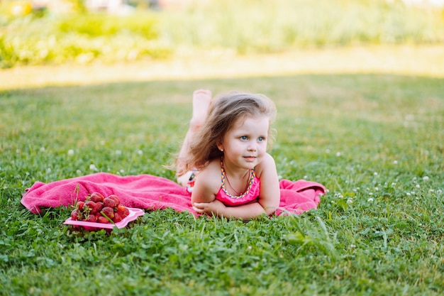 Adorable little girl lie on the grass with plate of fresh ripe strawberries and smile. childhood, immunity, happiness. Premium Photo