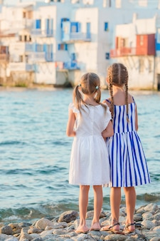 Adorable little girl at little venice the most popular tourist area on mykonos island, greece.