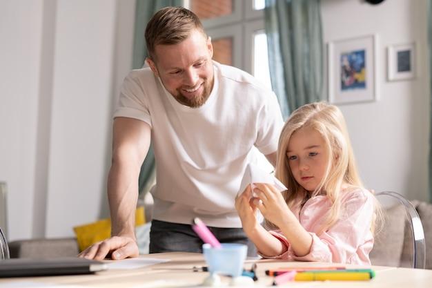 Очаровательная маленькая девочка смотрит на бумажную игрушку в руках, сидя за столом, а ее улыбающийся отец стоит рядом и склоняется над ней