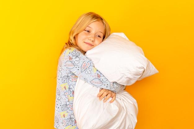 Очаровательная маленькая девочка, глядя в камеру и обнимая подушку на желтой стене.