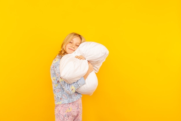 Adorable little girl looking at the camera and hugging a pillow background of a yellow wall.