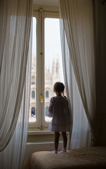 Adorable little girl looking out the window at duomo, milan, italy