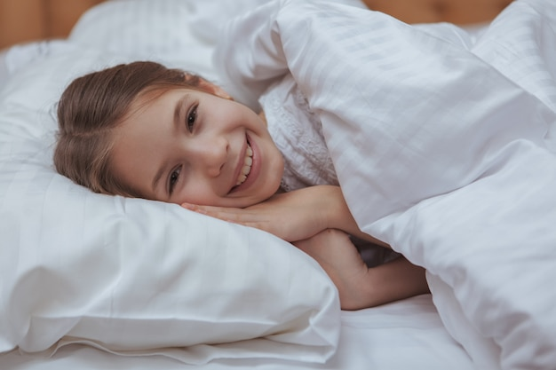 Adorable little girl lying in bed at home