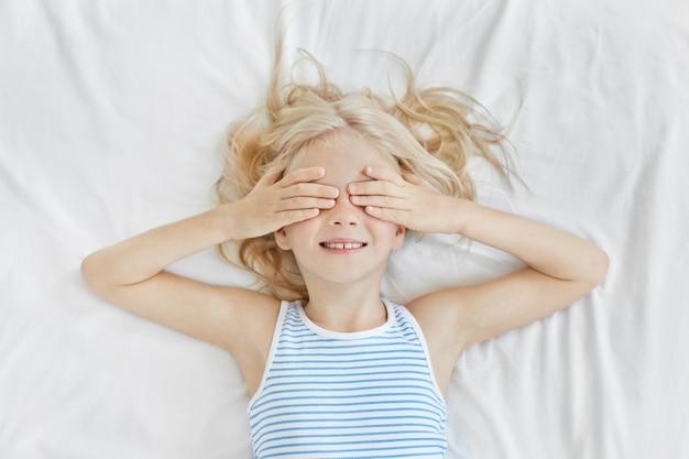 사랑스러운 작은 소녀 흰색 침구에 누워 손으로 그녀의 눈을 덮고 선원 티셔츠를 입고 수면 전에 웃 고. 주근깨가 자고 싶지 않은 침대에 재미와 금발 꼬마