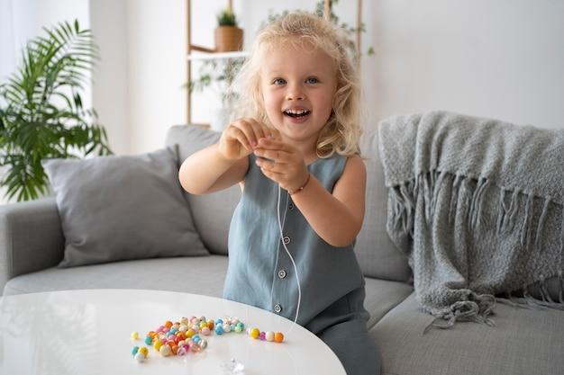 Adorabile bambina che fa accessori con diverse palline colorate