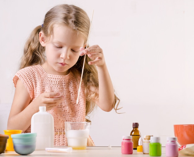 Adorable little girl making slime toy, meshes ingredients for  popular self made toy.