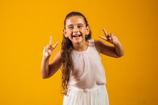 노란색 배경에 v 표시를 만드는 사랑스러운 어린 소녀. 좋은 분위기의 평화와 사랑