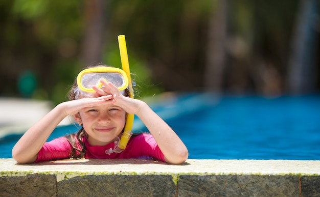 Adorable little girl at mask and goggles in swimming pool