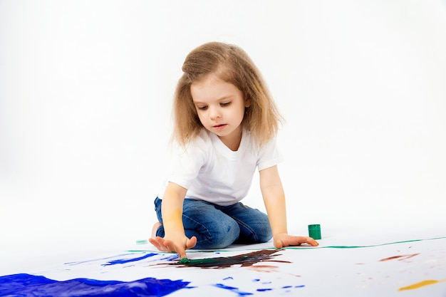 Adorable little girl, modern hair style, white shirt, blue jeans is drawing pictures by her hands with paints
