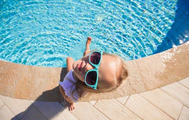 Adorable little girl near pool during tropical vacation