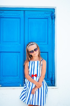 Adorable little girl at old street of typical greek traditional village on mykonos