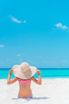 ビーチで愛らしい少女。幸せな女の子は海の青い空とターコイズブルーの水で夏休みをお楽しみください
