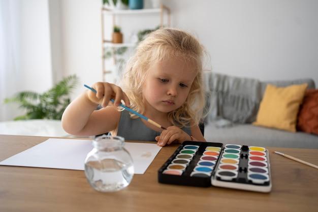 家で紙に絵を描く愛らしい少女