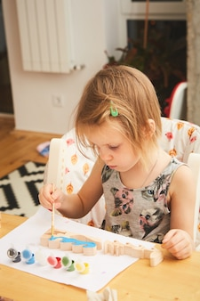 Adorable little girl painting in the room