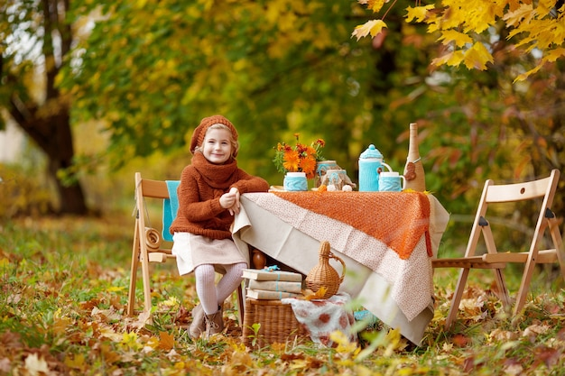 Adorable little girl on picnic in autumn park.