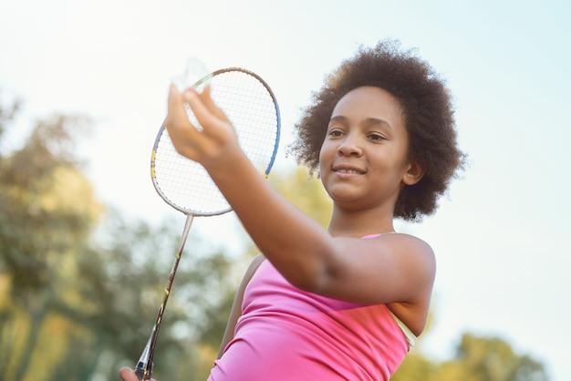 Очаровательная маленькая девочка играет в бадминтон на улице